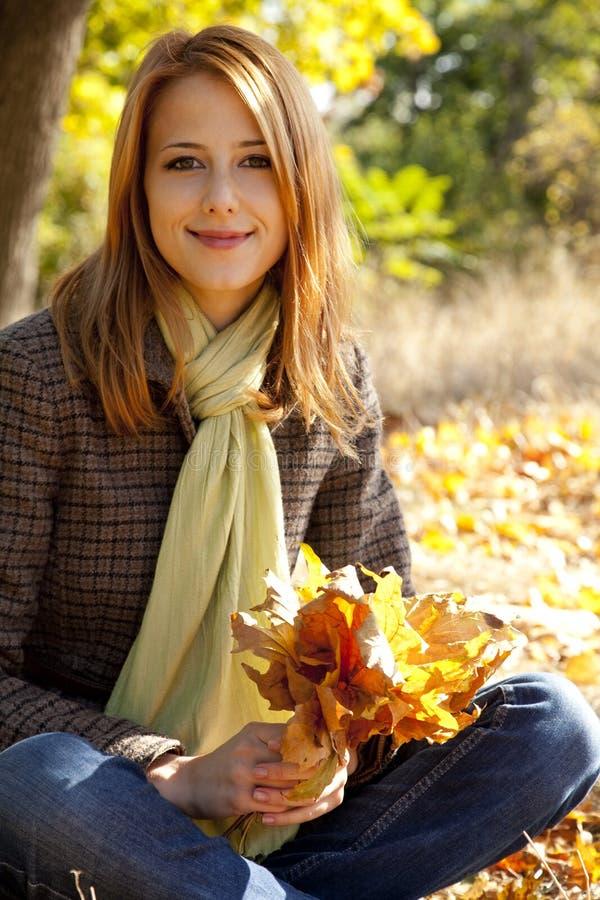 Retrato de la muchacha pelirroja en el parque del otoño foto de archivo