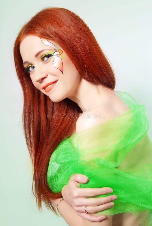 Retrato de la muchacha pelirroja hermosa con la flor pintada en su cara imagen de archivo