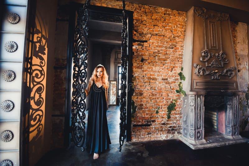 Retrato de la muchacha pelirroja hermosa joven en la imagen de una bruja gótica en Halloween imagen de archivo libre de regalías