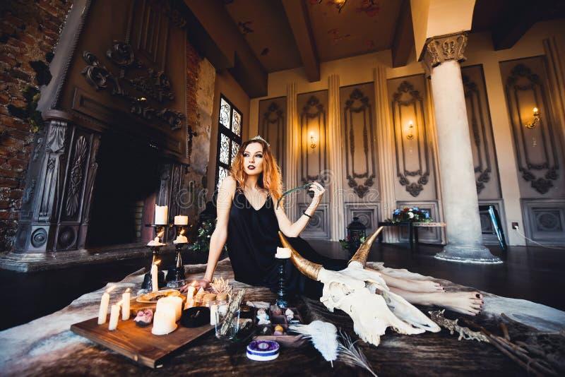 Retrato de la muchacha pelirroja hermosa joven en la imagen de una bruja gótica en Halloween foto de archivo