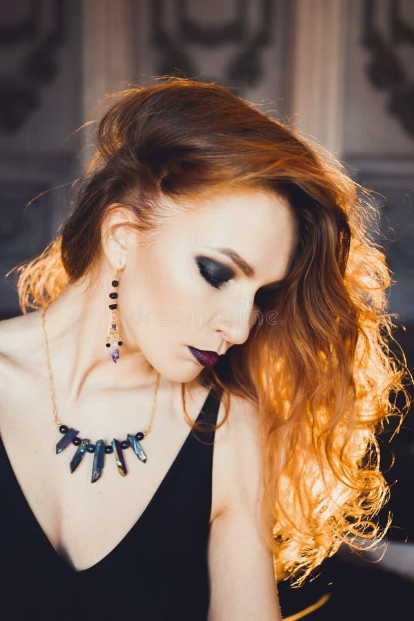 Retrato de la muchacha pelirroja hermosa joven en la imagen de una bruja gótica en Halloween fotografía de archivo