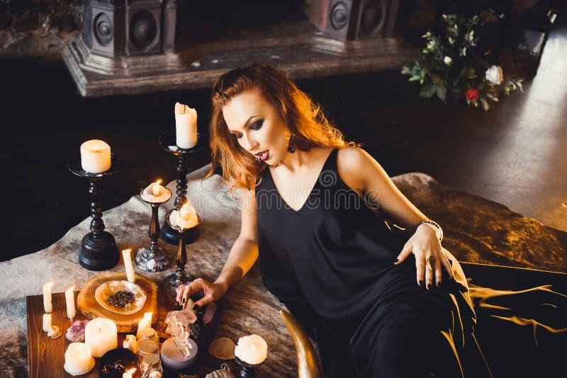 Retrato de la muchacha pelirroja hermosa joven en la imagen de una bruja gótica en Halloween foto de archivo libre de regalías