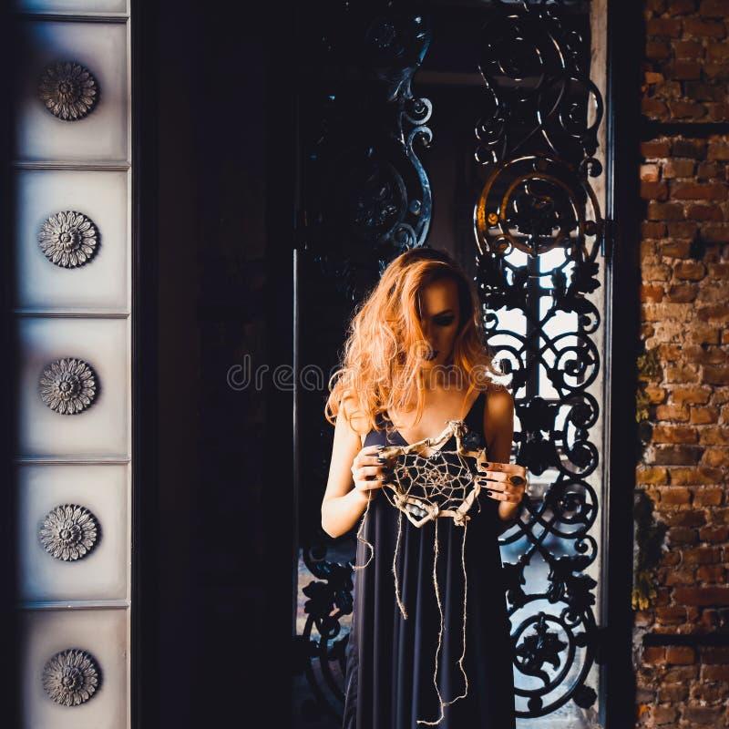 Retrato de la muchacha pelirroja hermosa joven en la imagen de una bruja gótica en Halloween fotos de archivo libres de regalías