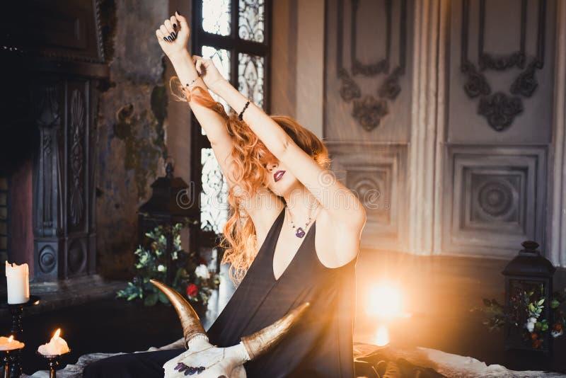 Retrato de la muchacha pelirroja hermosa joven en la imagen de una bruja gótica en Halloween imagenes de archivo