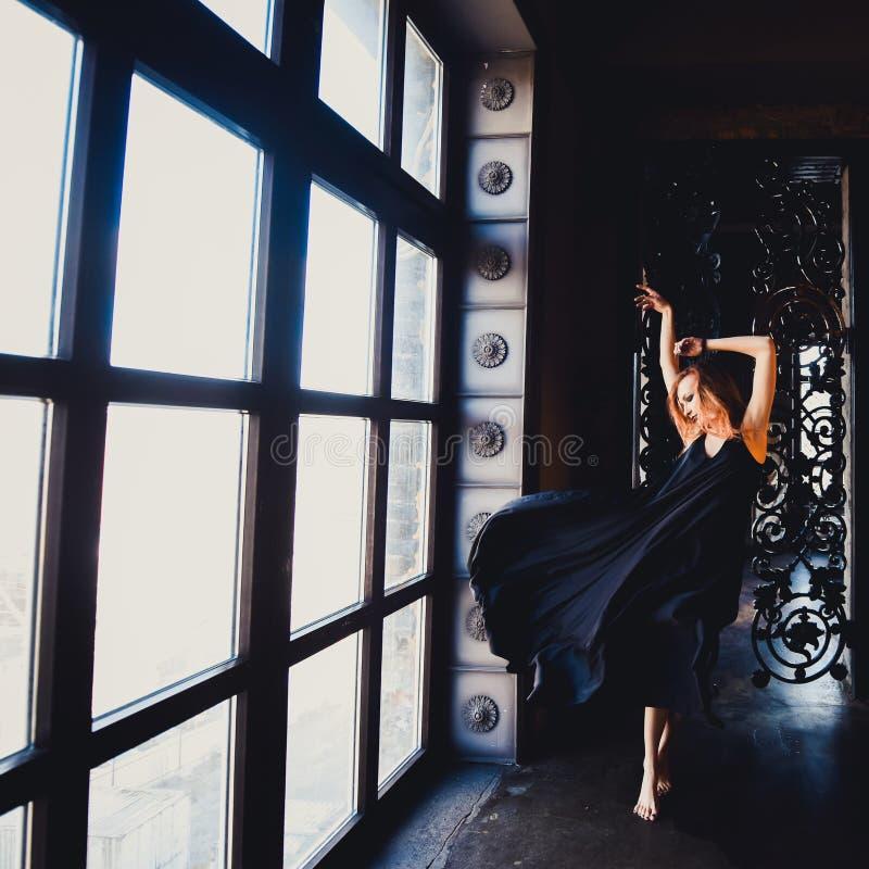Retrato de la muchacha pelirroja hermosa joven en la imagen de una bruja gótica en Halloween fotos de archivo