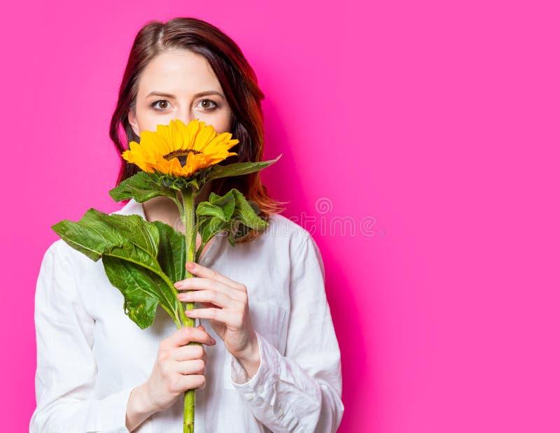 Retrato de la muchacha pelirroja joven con el girasol imagen de archivo