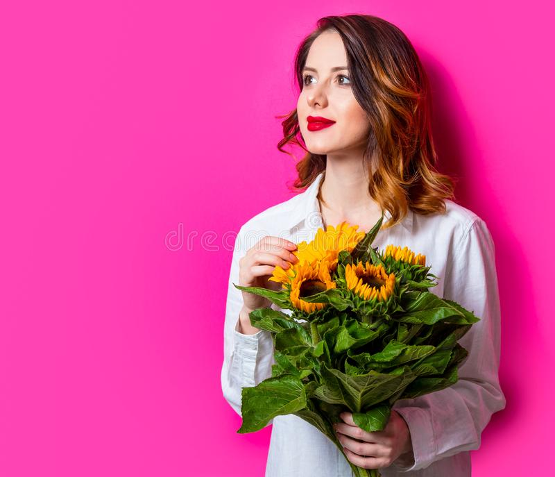 Retrato de la muchacha pelirroja joven con los girasoles imagen de archivo libre de regalías