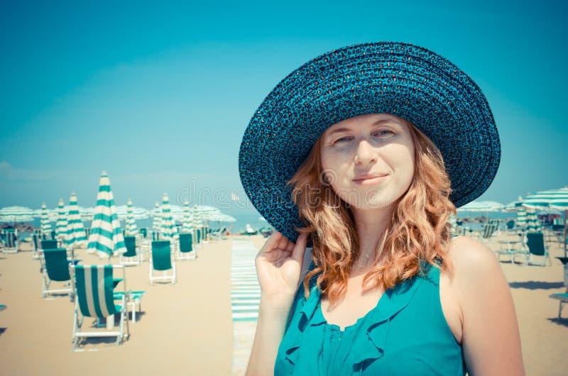 Retrato de la muchacha pelirroja sonriente en sombrero en la playa imagenes de archivo