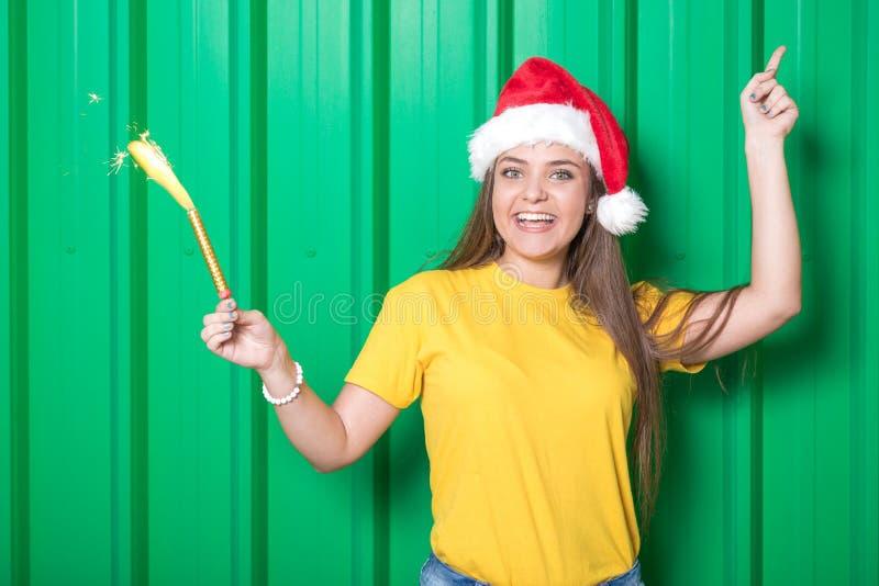 Retrato de la muchacha que celebra la Navidad con la bengala y el sombrero de Santa Claus foto de archivo