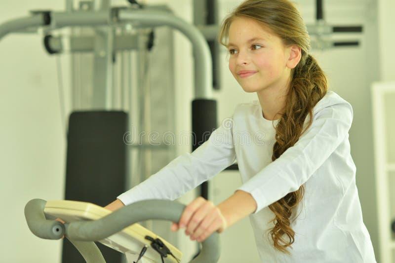 Retrato de la muchacha que hace ejercicios en la bici del exetcise en gimnasio foto de archivo