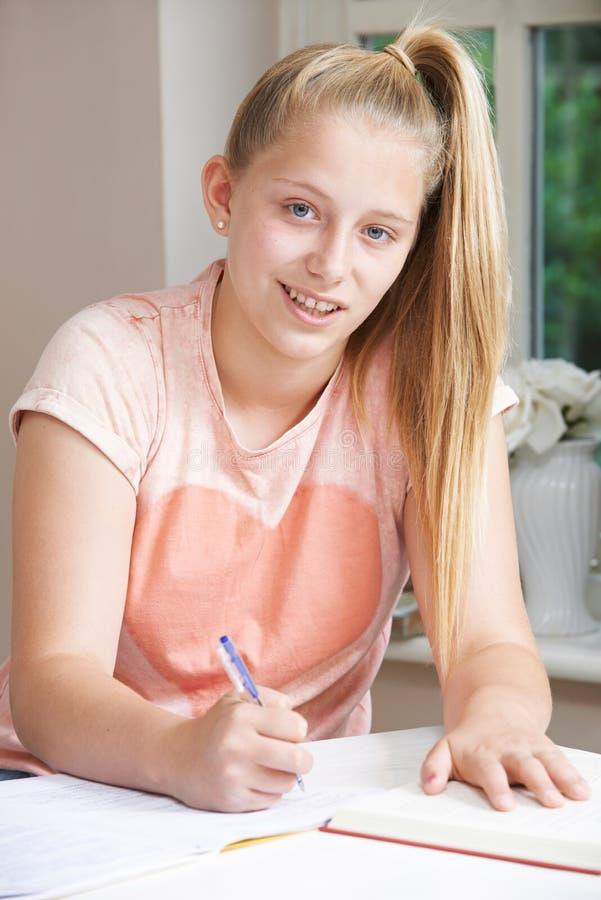 Retrato de la muchacha que hace la preparación en el escritorio foto de archivo libre de regalías