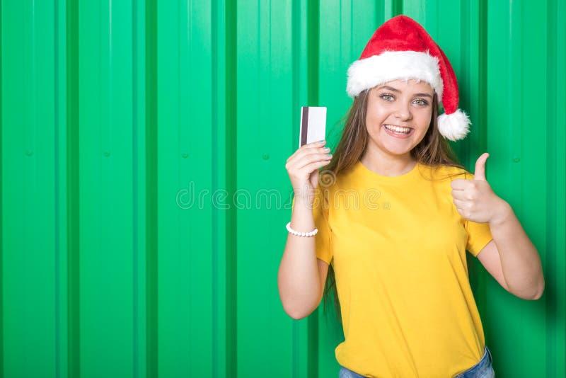 Retrato de la muchacha que lleva el sombrero de Santa Claus y que sostiene la tarjeta de crédito contra la pared verde del metal fotografía de archivo libre de regalías