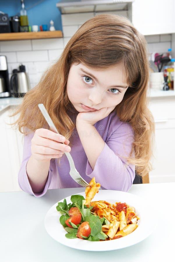 Retrato de la muchacha que no disfruta de la comida sana en casa foto de archivo libre de regalías
