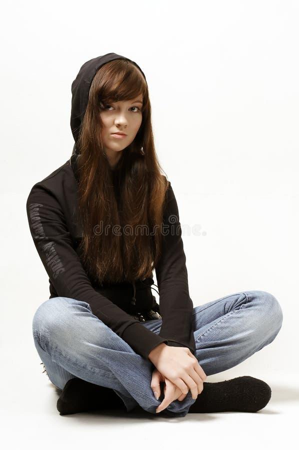Retrato de la muchacha que se sienta en pantalones vaqueros imagen de archivo libre de regalías
