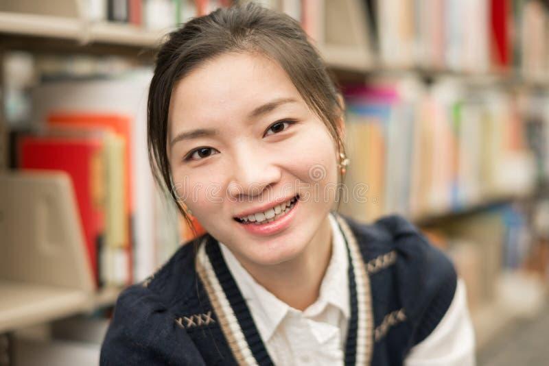 Retrato de la muchacha que sonríe en biblioteca imagen de archivo libre de regalías