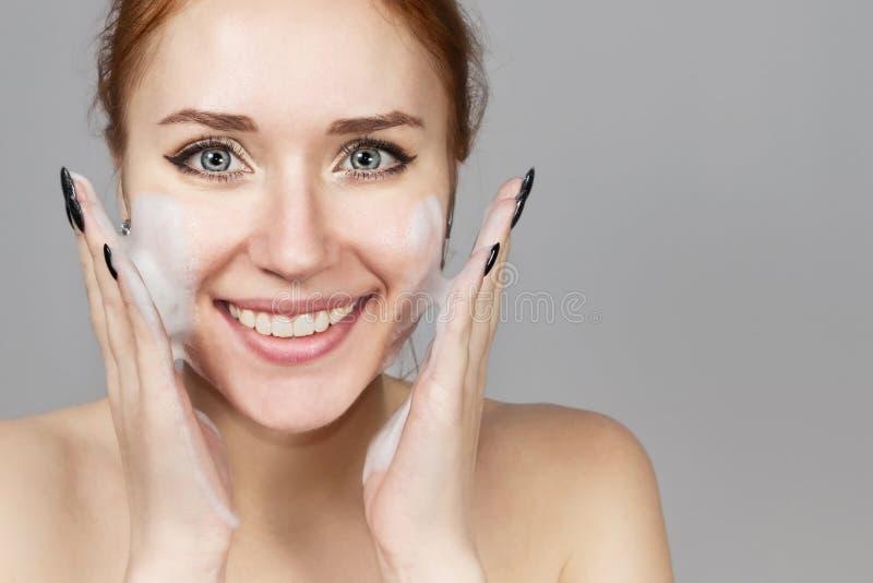 Retrato de la muchacha de risa alegre que aplica la espuma para lavarse en su cara Pelirrojo precioso de la mujer con aspecto atr imagen de archivo libre de regalías
