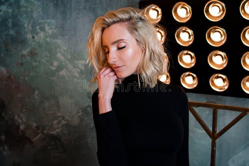 Retrato de la muchacha rizada atractiva hermosa elegante joven en suéter negro en la etapa foto de archivo libre de regalías