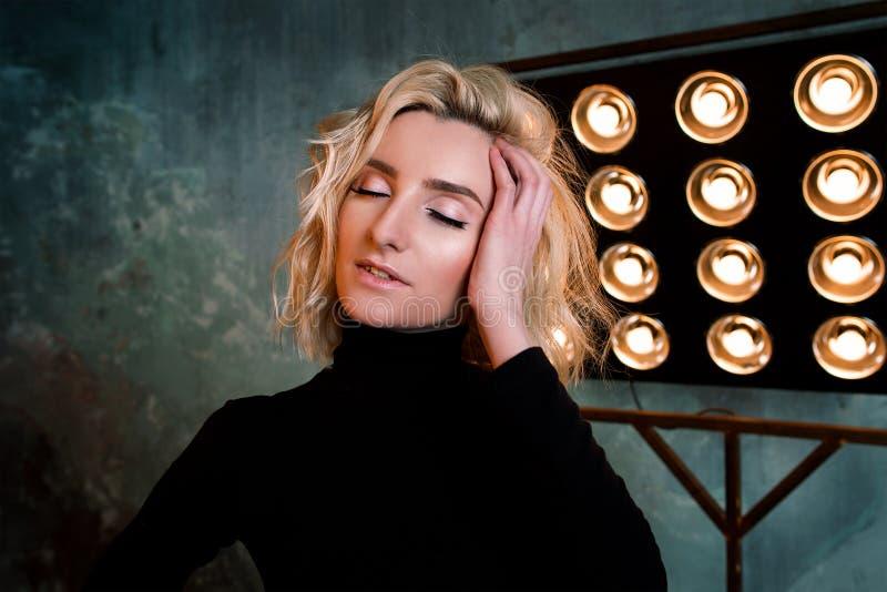 Retrato de la muchacha rizada atractiva hermosa elegante joven en suéter negro en la etapa imagen de archivo