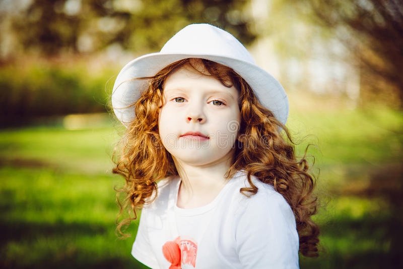 Retrato de la muchacha rizada en un sombrero blanco foto de archivo