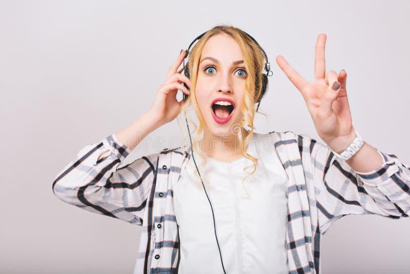 Retrato de la muchacha rizada rubia linda en música que escucha de los auriculares con la cara sorprendida y el baile El encantar imagenes de archivo