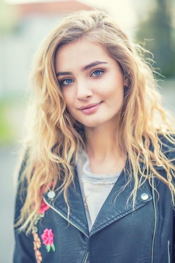 Retrato de la muchacha rubia atractiva con el pelo largo rizado y los ojos azules imagenes de archivo