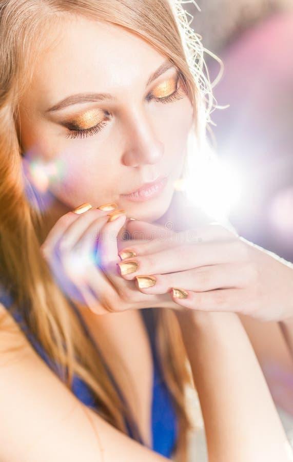 Retrato de la muchacha rubia atractiva con la manicura de oro de la moza descarada imágenes de archivo libres de regalías