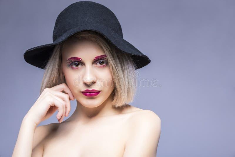 Retrato de la muchacha rubia cauc?sica hermosa en sombrero negro sobre Gray Background con maquillaje facial fotografía de archivo