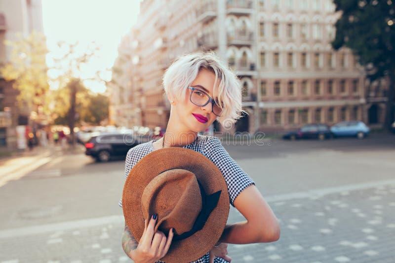 Retrato de la muchacha rubia con el pelo corto que mira a la cámara en el steet en fondo de la puesta del sol Ella lleva gris foto de archivo libre de regalías