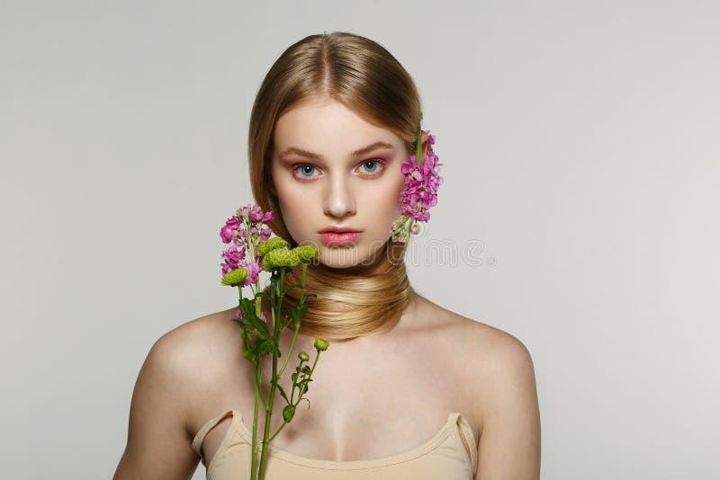 Retrato de la muchacha rubia fresca y hermosa con las flores rosadas imagenes de archivo