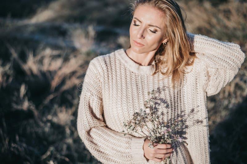 Retrato de la muchacha rubia joven en el suéter ligero caliente que es exterior imagen de archivo