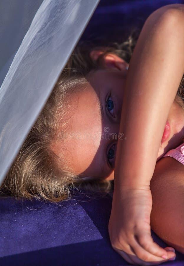 Retrato de la muchacha rubia que oculta el vacaciones fotografía de archivo