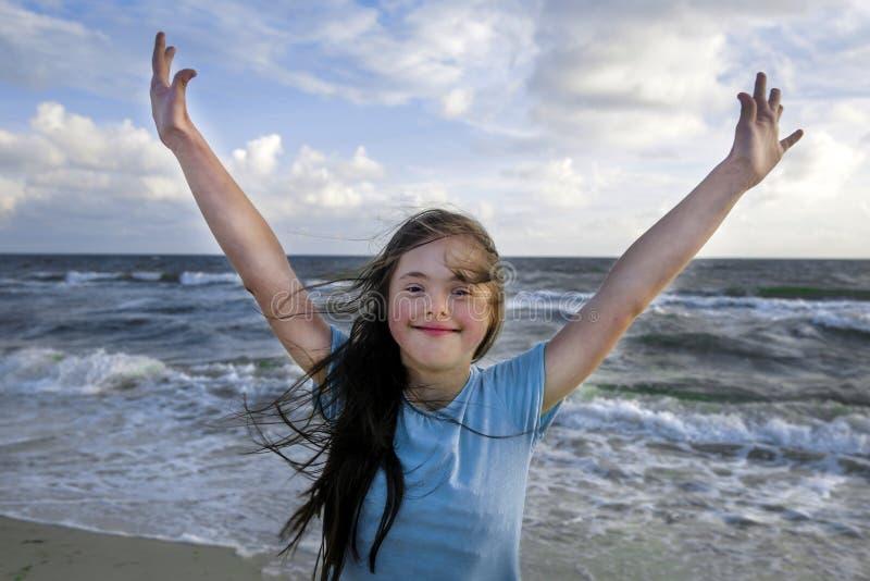 Retrato de la muchacha de Síndrome de Down que sonríe en el fondo del seaÑŽ imagenes de archivo