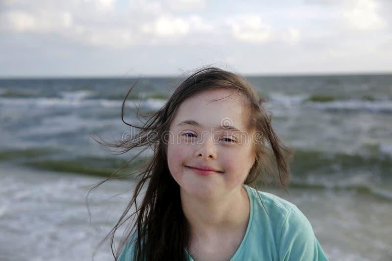Retrato de la muchacha de S?ndrome de Down que sonr?e en el fondo del mar imagenes de archivo