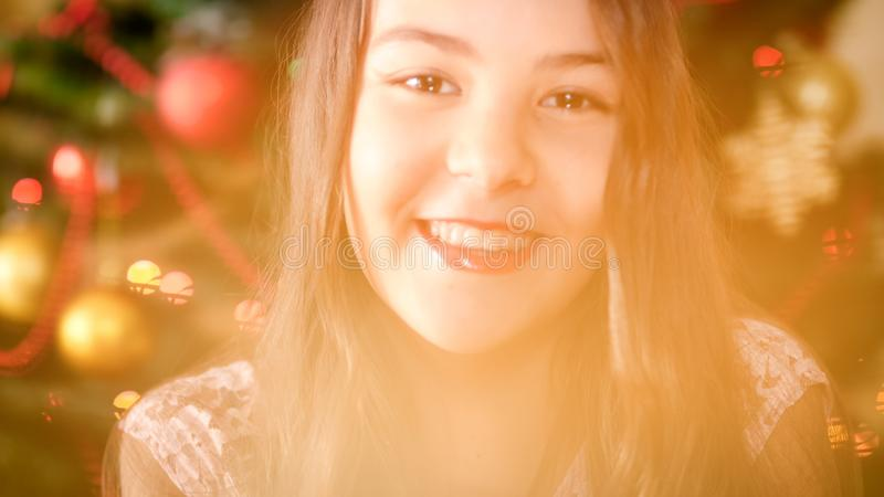 Retrato de la muchacha sonriente beautful que presenta contra el árbol de navidad decroated fotografía de archivo