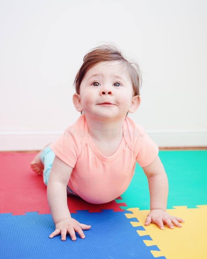 Retrato de la muchacha sonriente caucásica adorable linda del bebé que miente en piso en sitio de los niños fotografía de archivo libre de regalías