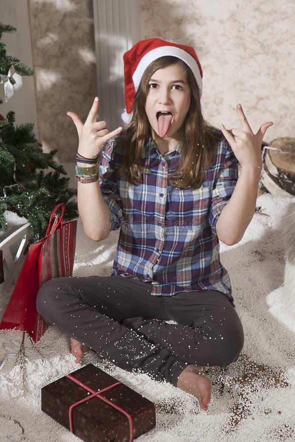 Retrato de la muchacha sonriente del adolescente en el sombrero de santa que lleva a cabo la Navidad imagen de archivo libre de regalías