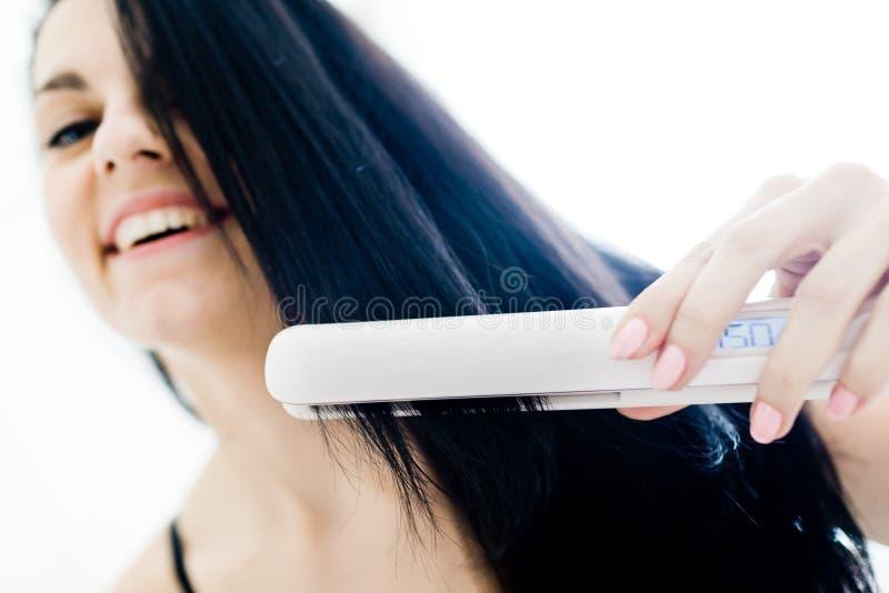 Retrato de la muchacha sonriente en cama con los pelos negros rectos usando la enderezadora imagen de archivo