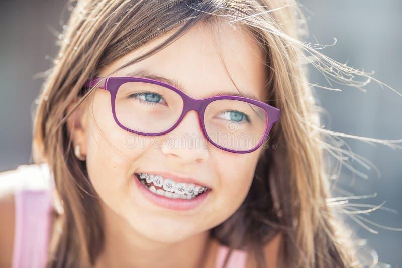 Retrato de la muchacha sonriente feliz con los apoyos y los vidrios dentales imagenes de archivo