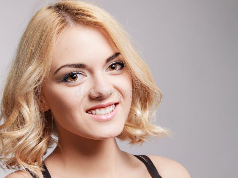 Retrato de la muchacha sonriente feliz que presenta en estudio fotografía de archivo