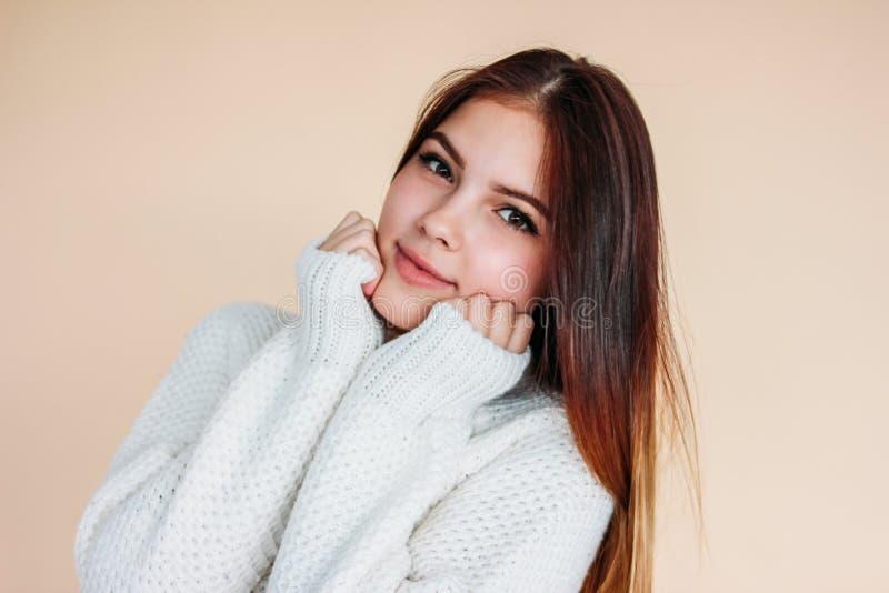Retrato de la muchacha sonriente hermosa del adolescente con la piel limpia y el pelo largo oscuro en suéter blanco acogedor en f foto de archivo libre de regalías
