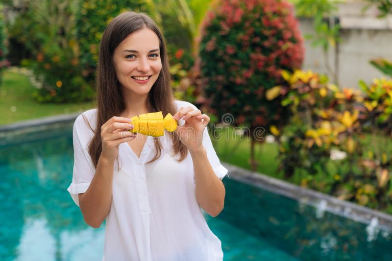 Retrato de la muchacha sonriente hermosa en la camisa blanca con el pedazo de mango en sus manos fotos de archivo