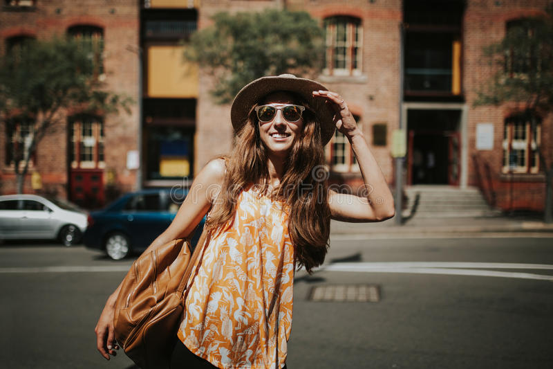 Retrato de la muchacha sonriente linda en gafas de sol con los edificios de la ciudad en el fondo imágenes de archivo libres de regalías