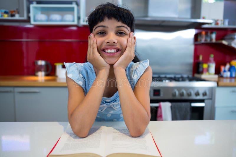 Retrato de la muchacha sonriente que se sienta con la novela en cocina imágenes de archivo libres de regalías
