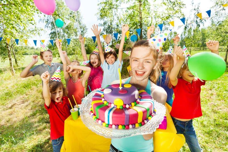 Retrato de la muchacha sonriente que sostiene la torta de cumpleaños fotografía de archivo