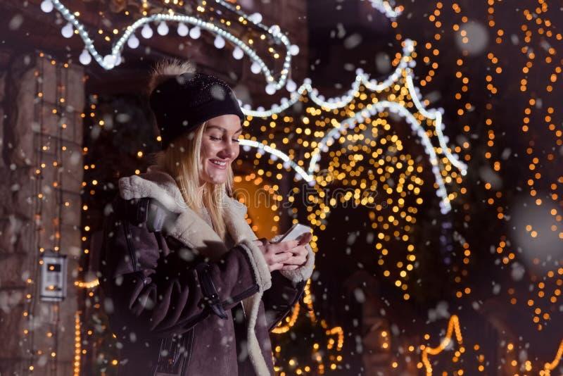 Retrato de la muchacha sonriente rubia hermosa que usa el teléfono elegante en f imagen de archivo