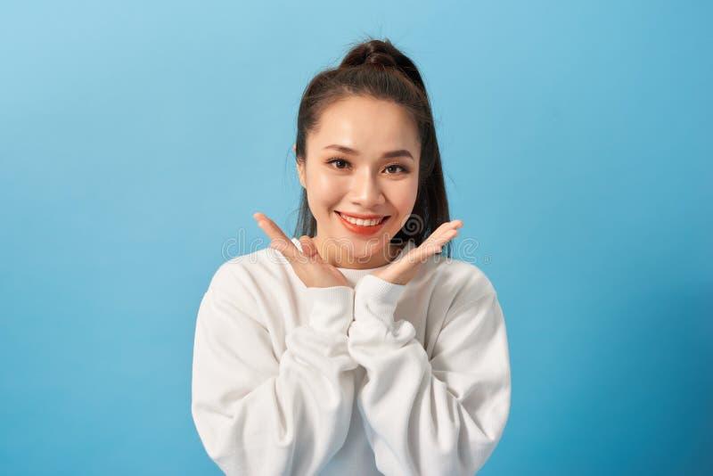 Retrato de la mujer adulta adorable despreocupada alegre que sonríe ampliamente y que sostiene las palmas cerca de mejillas, sien fotos de archivo