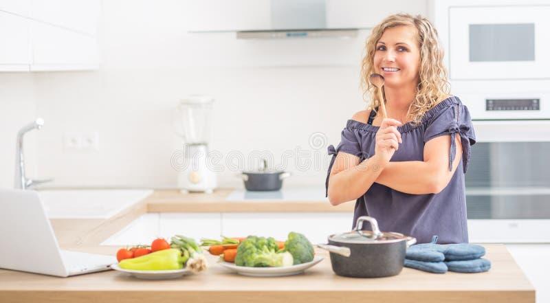 Retrato de la mujer adulta feliz en su cocina moderna con el pote y las verduras foto de archivo libre de regalías