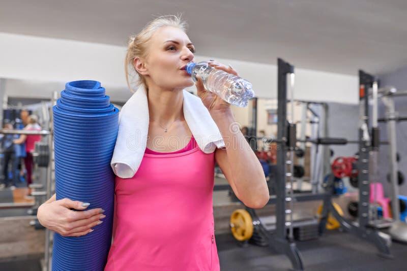 Retrato de la mujer adulta sonriente con la botella de agua y de estera de los deportes en club de salud Concepto del deporte de  imagen de archivo libre de regalías