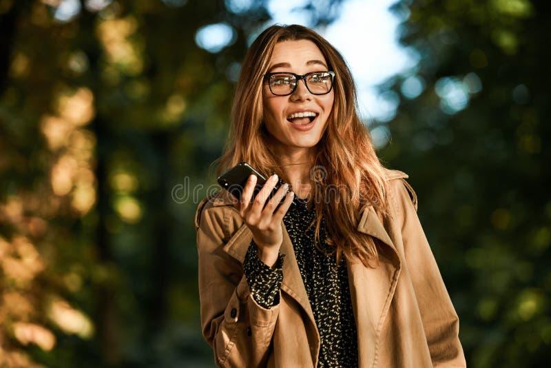 Retrato de la mujer afable que usa el teléfono celular mientras que camina a través del bulevar vacío fotos de archivo
