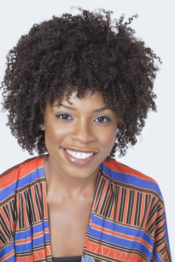 Retrato de la mujer afroamericana bonita en desgaste tradicional que sonríe sobre fondo gris imágenes de archivo libres de regalías